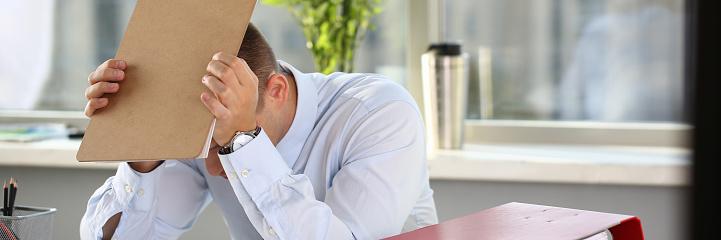 690496350 istock photo A man experiences stress and a headache 1075734228
