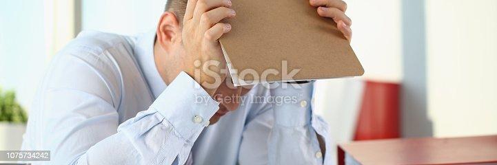 690496350istockphoto A man experiences stress and a headache 1075734242