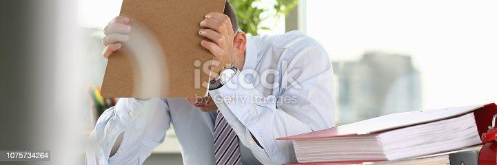 690496350istockphoto A man experiences stress and a headache 1075734264