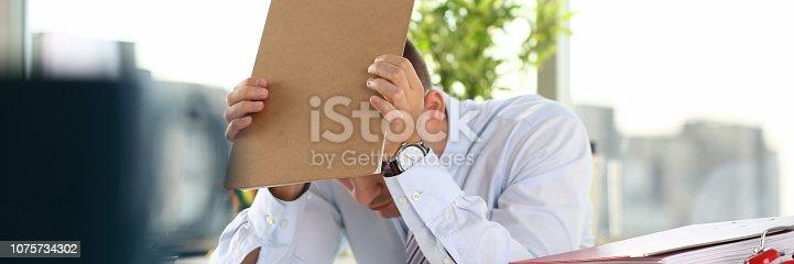 690496350istockphoto A man experiences stress and a headache 1075734302
