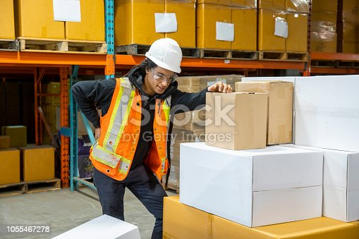 A male worker experiencing lower back pain at work in an industrial warehouse.