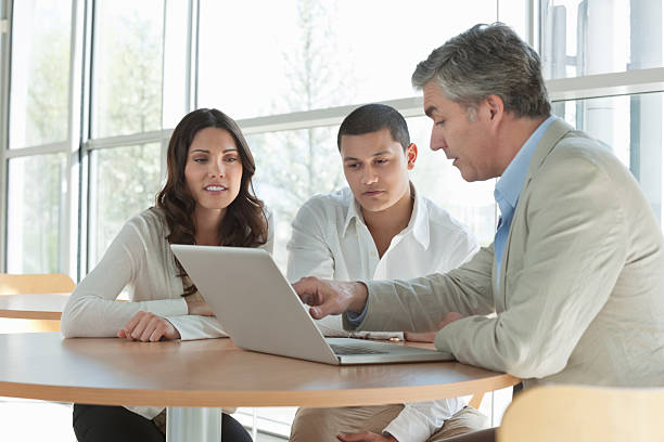 man explaining an investment plan to couple - financial advisor with clients stock photos and pictures