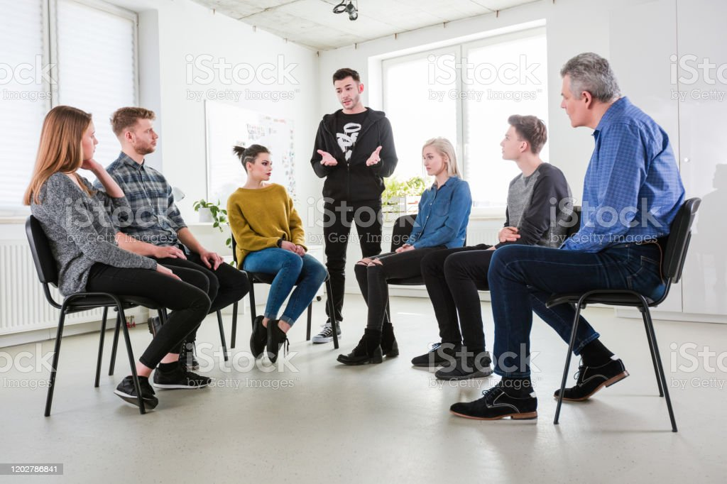 Man explaining problems to friends and therapist Young man gesturing while explaining problems in group therapy. Mental health professional is having meeting with students in lecture hall. They are wearing casuals. 18-19 Years Stock Photo