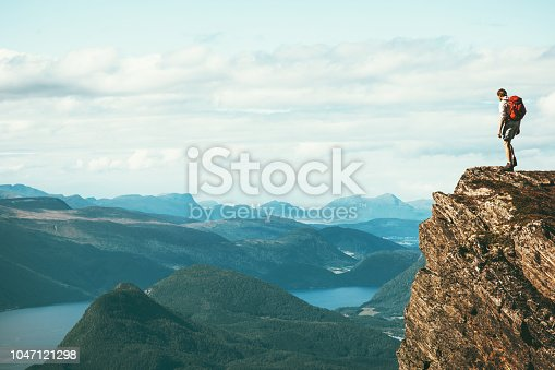 Man explorer standing on cliff alone mountain summit over fjord Norway landscape Travel Lifestyle success motivation concept adventure active vacations outdoor