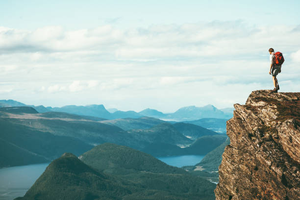 man explorer standing on cliff alone mountain summit over fjord norway landscape travel lifestyle success motivation concept adventure active vacations outdoor - szczyt zdjęcia i obrazy z banku zdjęć
