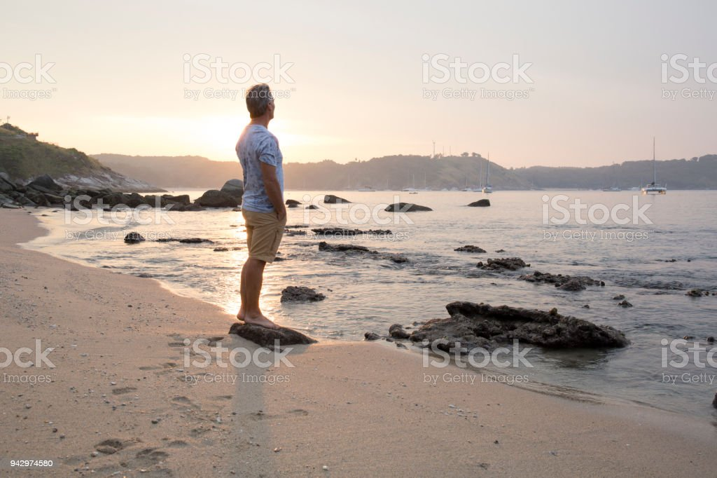 Man explores beach at sunrise stock photo