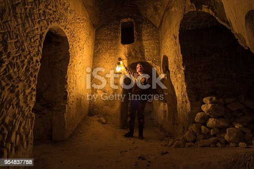 Man explores narrow passage in ancient abandoned underground chalky cave monastery.
