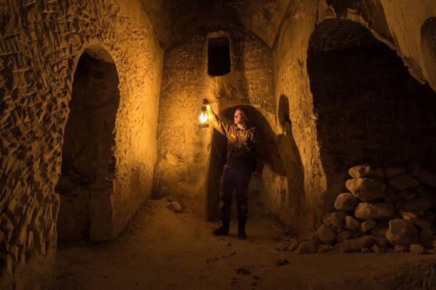 고 대 버려진된 지 하 백 악 질 동굴 수도원에서 좁은 통로 탐구 하는 남자 - 속이 빈 뉴스 사진 이미지