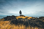 Man standing on colorful volcanic coast in Iceland.
