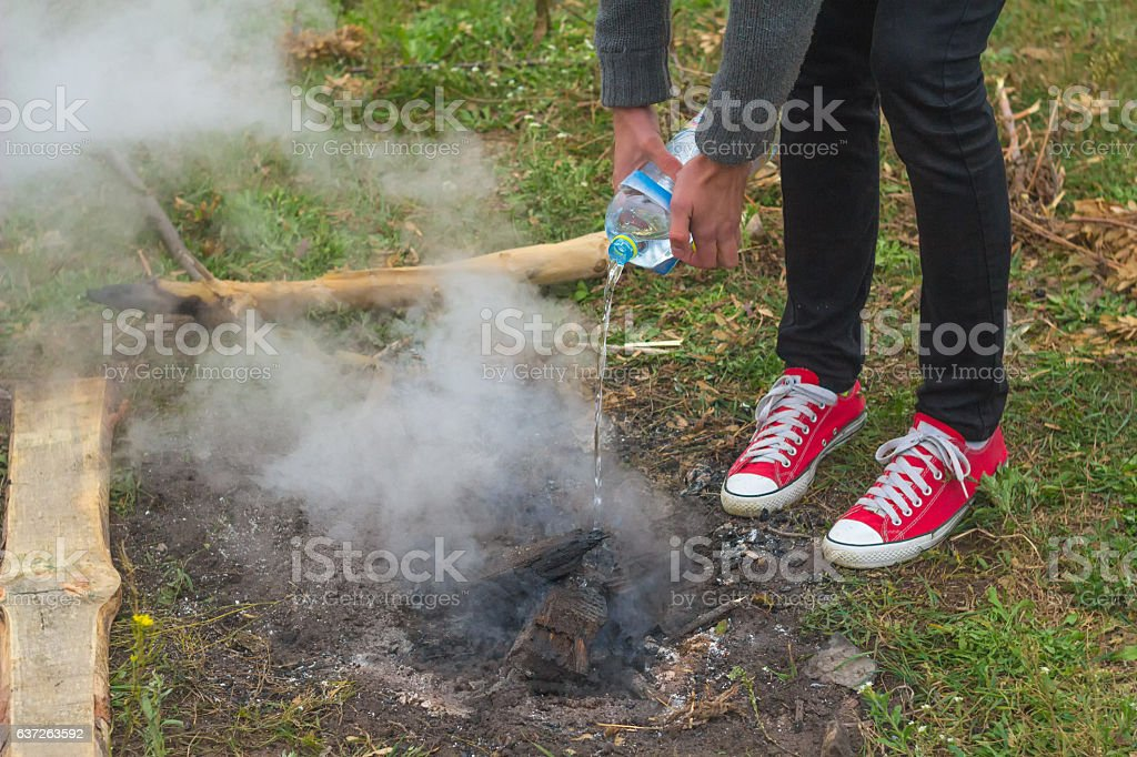 Man Extinguishing a campfire with Water From Plastic Bottle stock photo