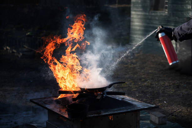 Man extinguishing the fire on an iron pan with foam from a spray can, demonstration during a fire department training, dark background with copy space Man extinguishing the fire on an iron pan with foam from a spray can, demonstration during a fire department training, dark background with copy space extinguishing stock pictures, royalty-free photos & images
