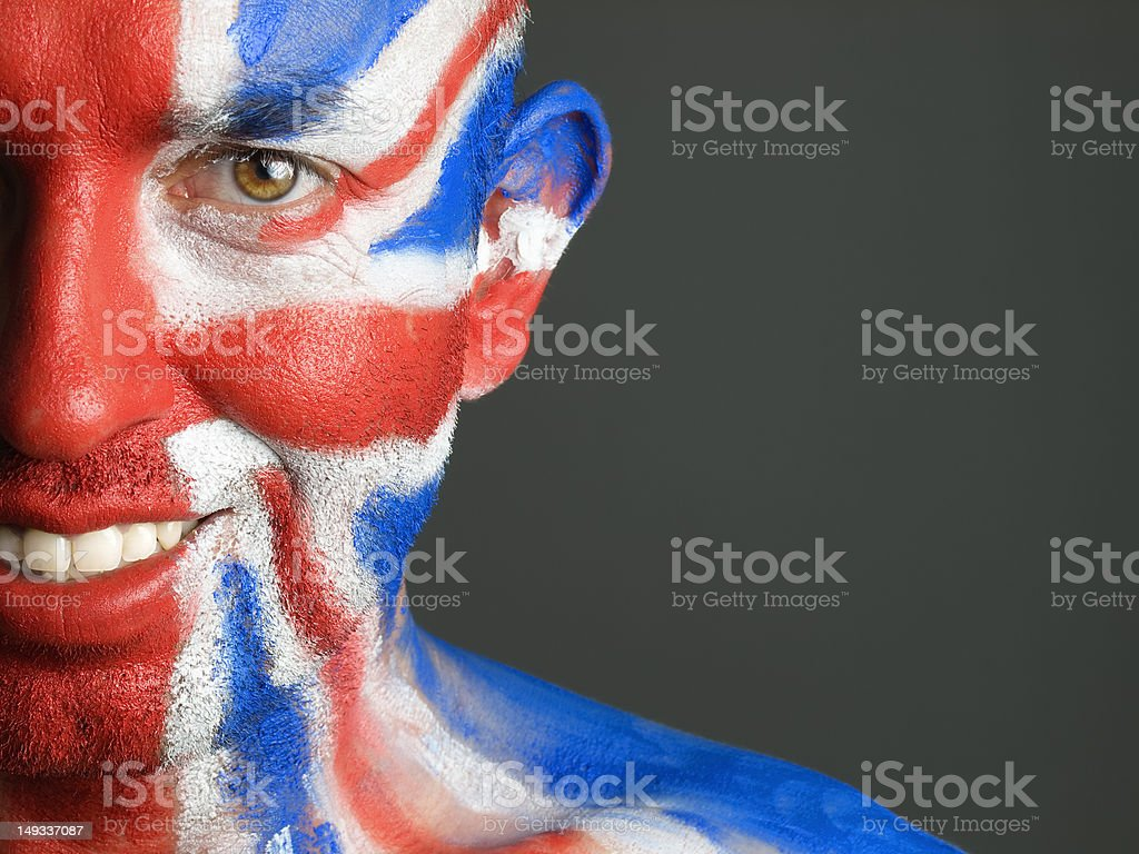 Man face painted with flag of United Kingdom, smiling expression. stock photo