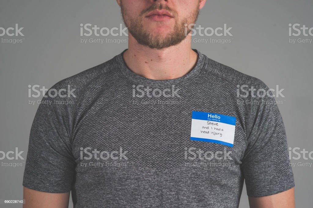 Young Caucasian man facing camera with name tag \'I had a head injury\'