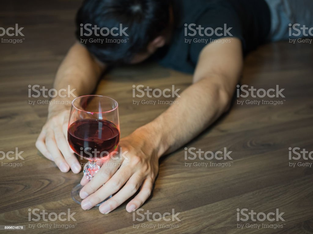 Man fall down drinking wine alcohol, pass out on the floor stock photo