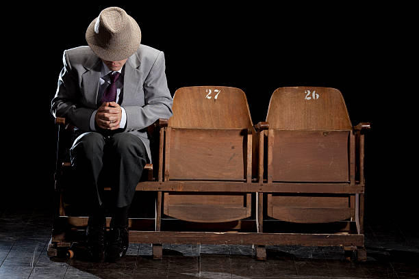 man falling asleep on theatre chair. - man face down stock pictures, royalty-free photos & images