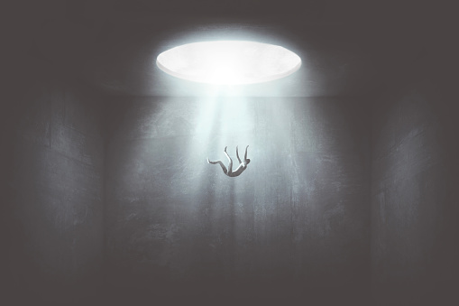 istock man falling down from a hole of light, surreal concept 1207309866
