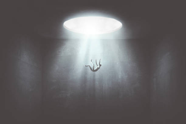 man falling down from a hole of light, surreal concept stock photo