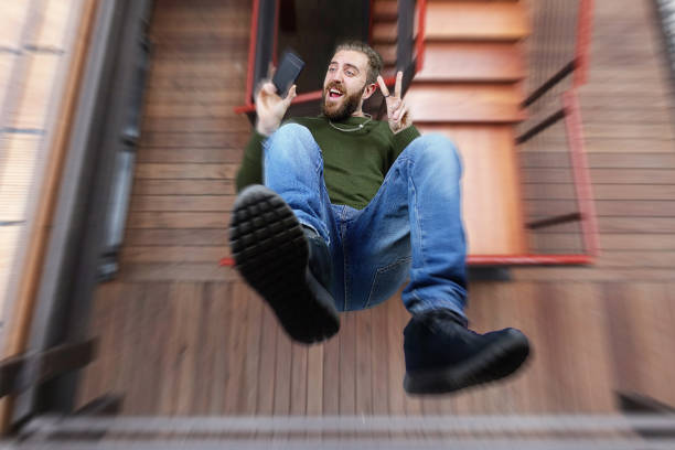 Man falling from the balcony and taking a selfie - foto stock