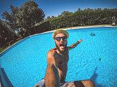 Man falling backward in swimming pool selfie shot.