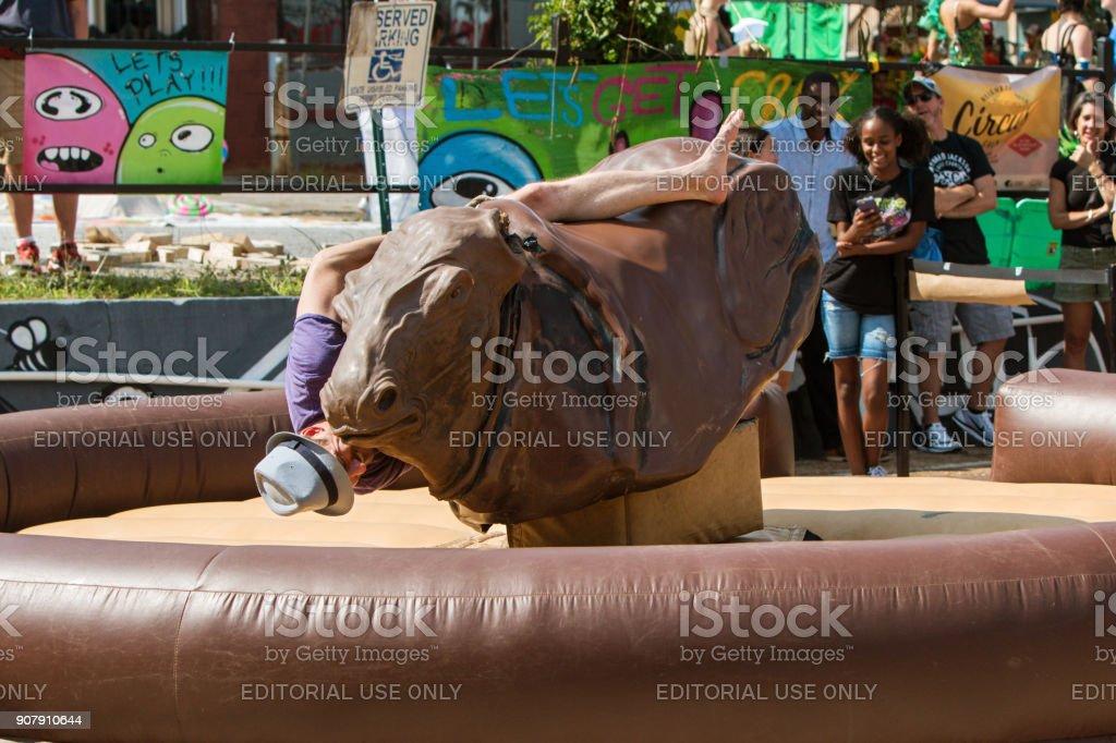 Man Falling Off Mechanical Bull Desperately Holds On stock photo