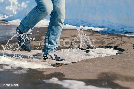 istock Man falls into a snow puddle in the asphalt with his foot. Close-up legs. 1159214609