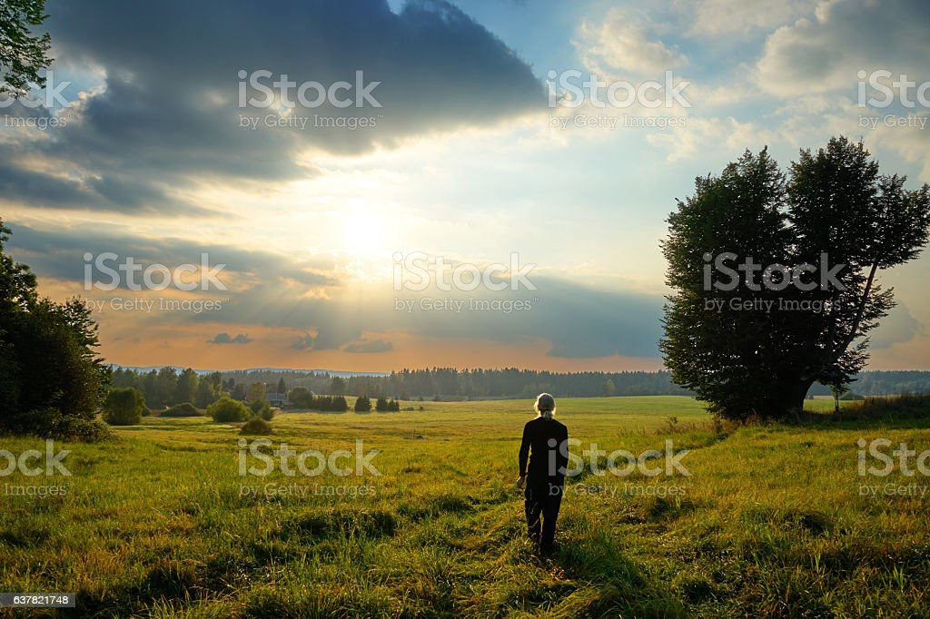 Man fascinated by the mystical glow of the sunset stock photo