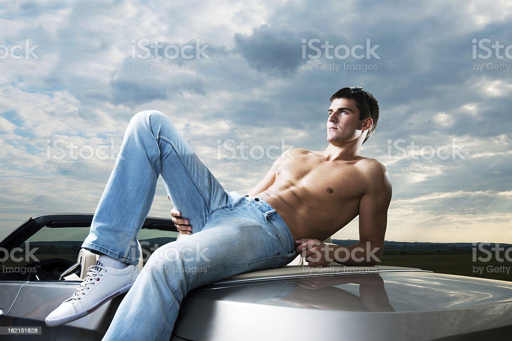Man fashion model lying on the cabriolet car. royalty-free stock photo