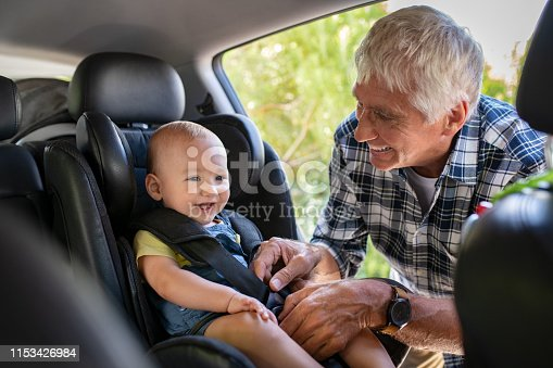 Grandfather tying baby in child seat. Cute little boy going for road trip with grandfather. Happy senior man and happpy smiling grandchild enjoying car trip. Toddler boy buckled into car seat.