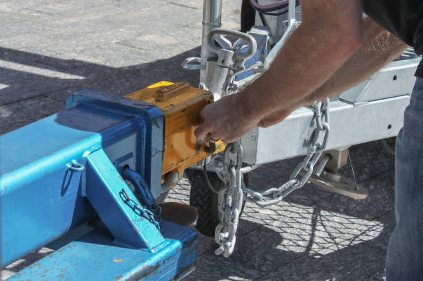 Man fastening a chain onto an industrial hitch on a trailer - close-up Man fastening a chain onto an industrial hitch on a trailer - close-up coupling device stock pictures, royalty-free photos & images