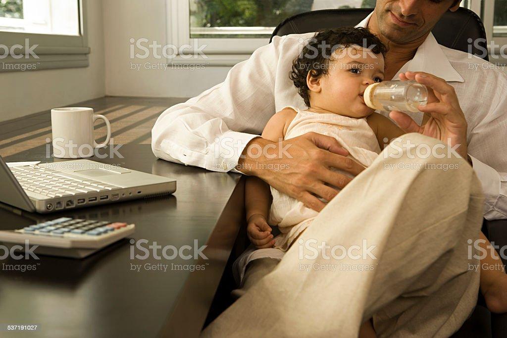 Man feeding baby stock photo