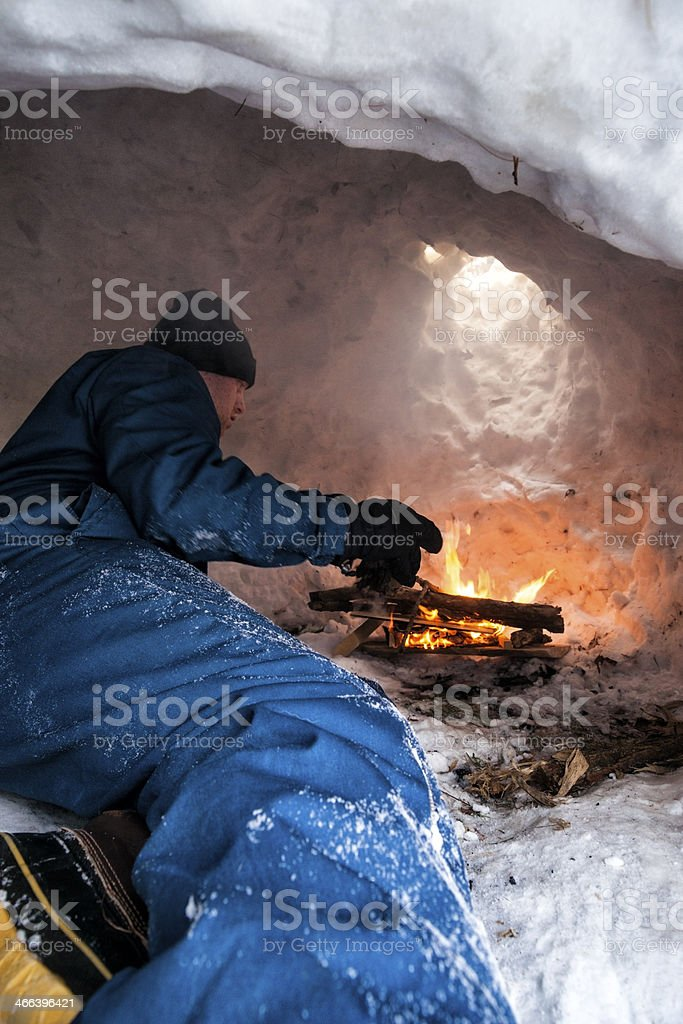 man feeds a fire inside an igloo stock photo more. Black Bedroom Furniture Sets. Home Design Ideas