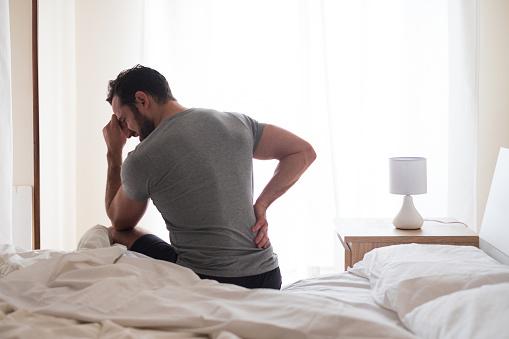 istock Man feeling backache after sleeping in bed 1066654634