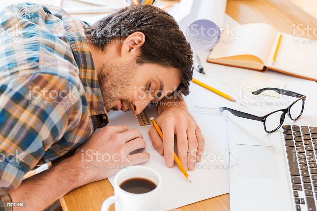 Man feeling exhausted and sleeping on working desk stock photo