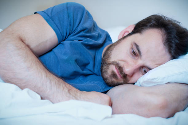 Man feeling negative emotions trying to sleep at night stock photo