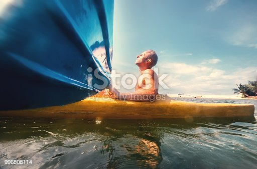 Man feeling the sun light on his face when he sails in canoe in tropical lagoon