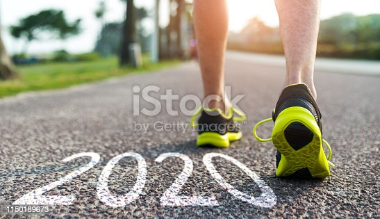 istock Man feet and number 2020 on the road 1150189673