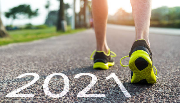 Man feet and number 2021 on the road stock photo