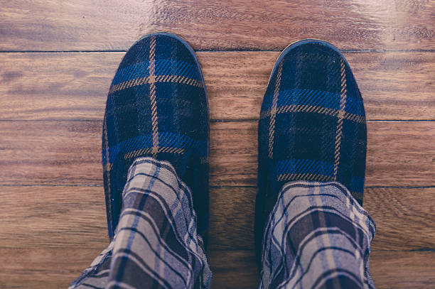 Man feet at home in pajamas and winter slippers stock photo