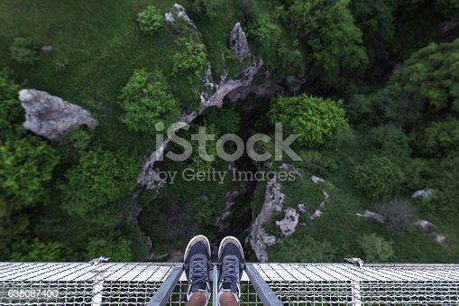 Man Feet standing on the edge of suspension bridge in Khndzoresk