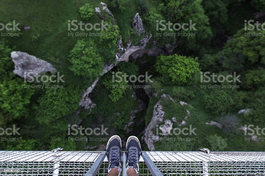 Man Feet standing on the edge of suspension bridge - foto de stock