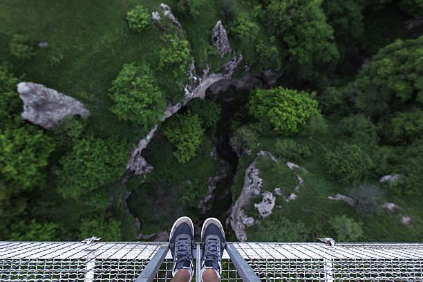 Man Feet standing on the edge of suspension bridge stock photo