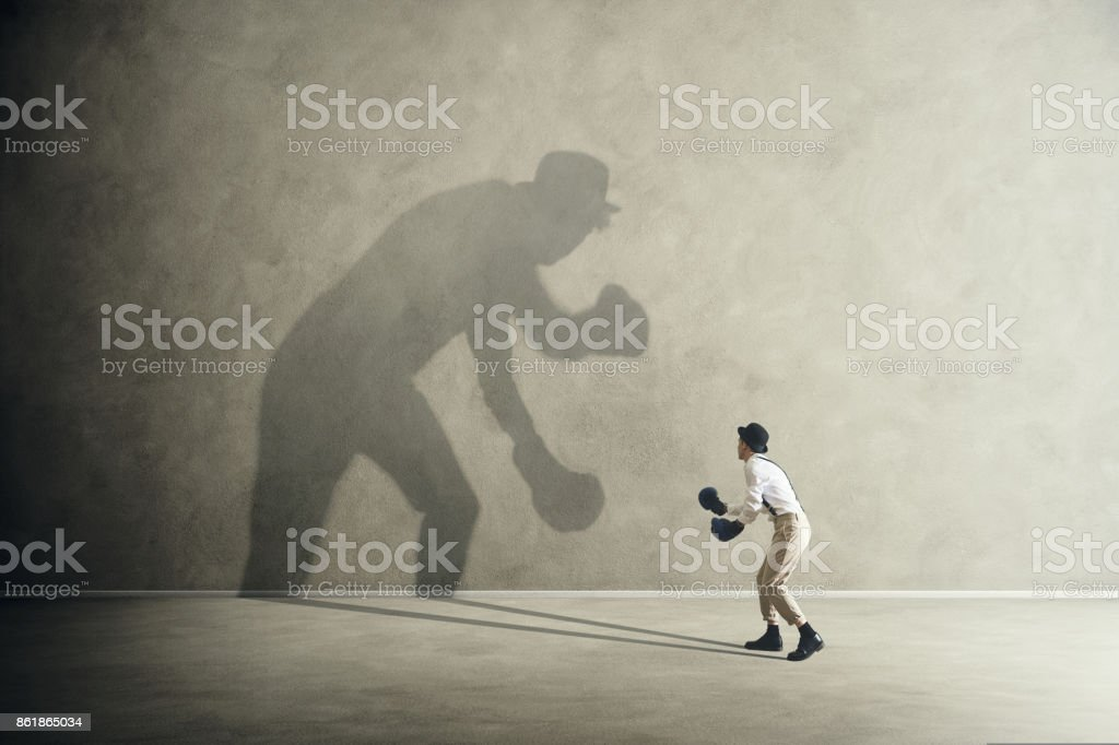 man fighting with his shadow, facing fears royalty-free stock photo