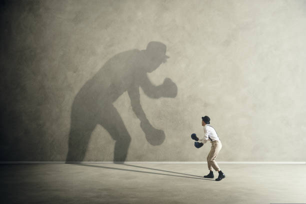 man fighting with his shadow, facing fears stock photo