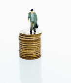 Man figurine standing on stack of coins