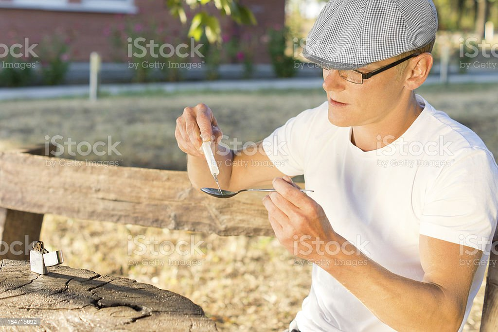 Man filling a syringe with soluble crack cocaine royalty-free stock photo