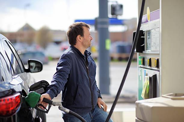 hombre en coche de combustible de llenado de carburante - echar combustible fotografías e imágenes de stock