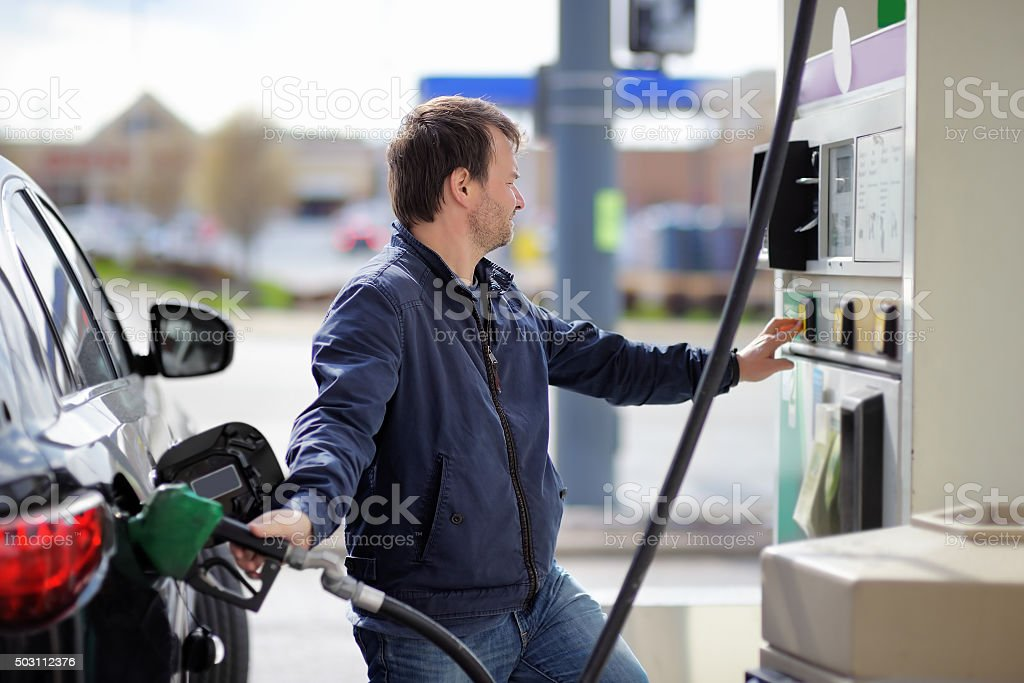 Man filling gasoline fuel in car stock photo