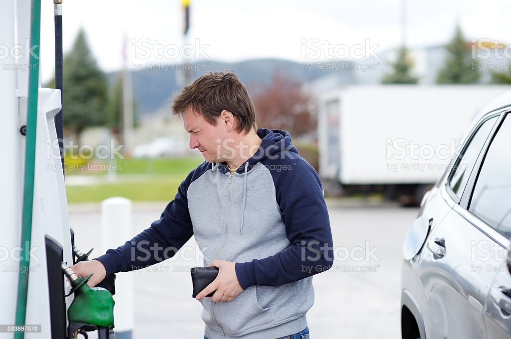 Man filling gasoline fuel in car stock photo