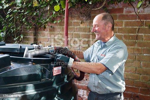 Buckingham, UK - September 13, 2014. Man filling a bunded oil tank with domestic heating oil (kerosene) at a home in rural England, UK