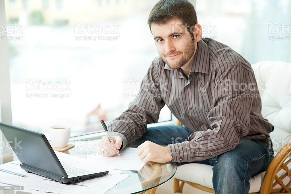 Man filling out a form looking at camera royalty-free stock photo
